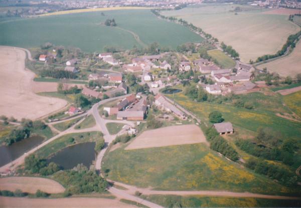 letecký snímek Kosova z let 1990-95, ještě zachovalá stodola.