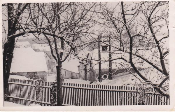 Kosov v zimě. Snímek zachycuje v levé části obecní kovárnu. Rok 1955, začátky kolektivizace.